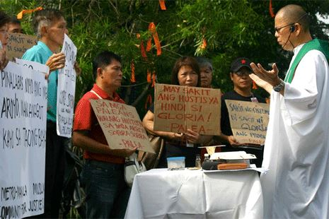 Father Robert Reyes leads the rally against a court order allowing Arroyo to travel.  Nov. 16, 2011